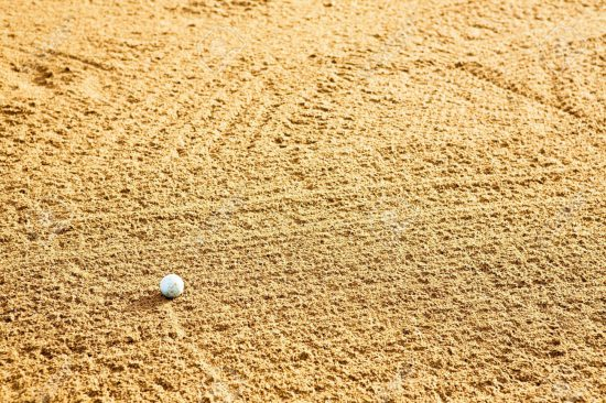 3418758-A-golf-ball-in-a-sand-trap-Stock-Photo